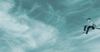 Funambolo seduto in equilibrio sulla corda